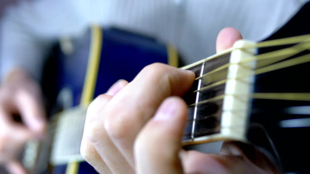 Musician Clamps the Chords on the Acoustic Guitar Frets. Slow motion