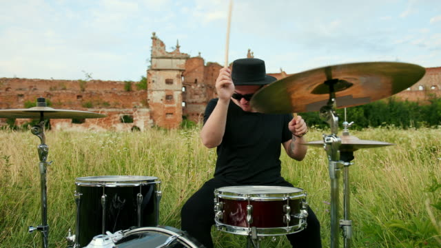 musiker trummis klädd i svarta kläder, hatt, spela trumset och cymbaler - trumset bildbanksvideor och videomaterial från bakom kulisserna