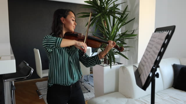 Musician exercising violin at home