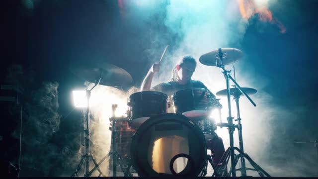 musiker spelar trumman som i den mörka grumlade studion. male drummer spelar trummor i rök. - trumset bildbanksvideor och videomaterial från bakom kulisserna