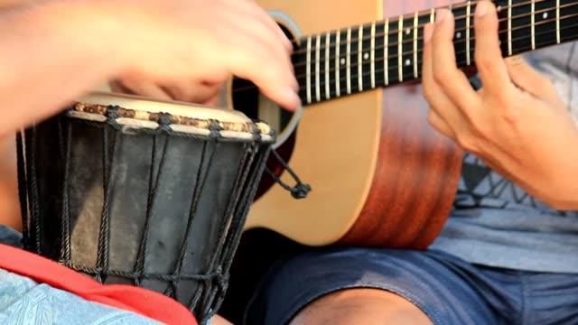 vídeos de stock, filmes e b-roll de um músico misturado jogando com bateria e guitarra - arte, cultura e espetáculo