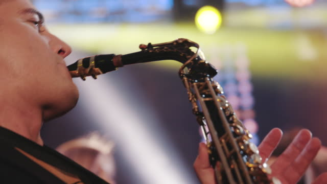 Musician playing alto saxophone on a gig, playing the saxophone