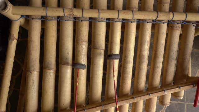 vidéos et rushes de musicien jouant l'instrument musical de bambou de bali rindik - instrument à percussion