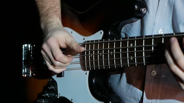 Musician playing bass guitar, close up view.