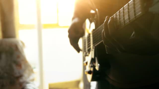 vídeos de stock e filmes b-roll de musician playing electric guitar melody at home - afro americano
