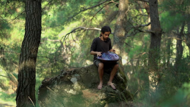 Musician playing handpan in forest (sound/audio available)
