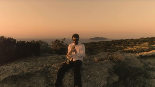 Musician playing saxophone sitting on the edge of a cliff on an island in front of the ocean at sunset video