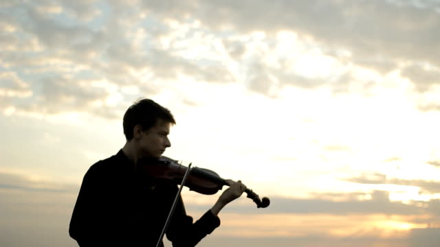 musician playing violin on the roof, classic music - top nero video stock e b–roll
