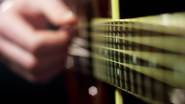 vídeos de stock, filmes e b-roll de um músico toca violão clássico e prática para jogar melhor e melhor. o guitarrista arranca as cordas com a mão. - música acústica