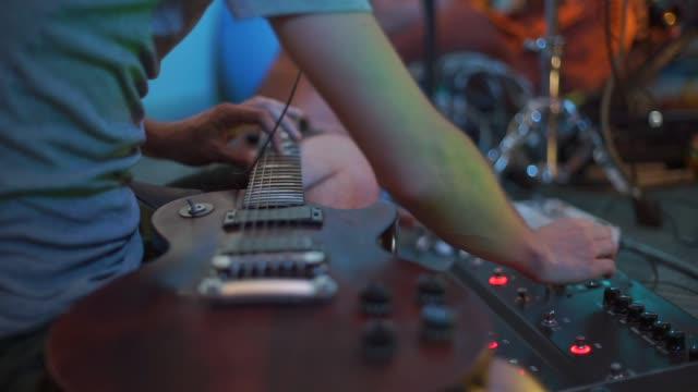 vídeos de stock e filmes b-roll de musician plays guitar and mixer at the same time - compositor