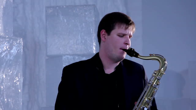 Musician plays the saxophone in the studio (dolly shot) video