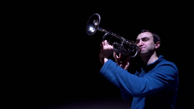 A musician plays the trumpet, isolated black background video