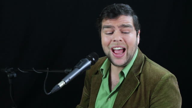 Musician sings into microphone video