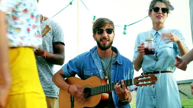 ギターとウクレレと歌、それらのまわりで踊って友人ミュージシャン - ミュージシャン点の映像素材/bロール