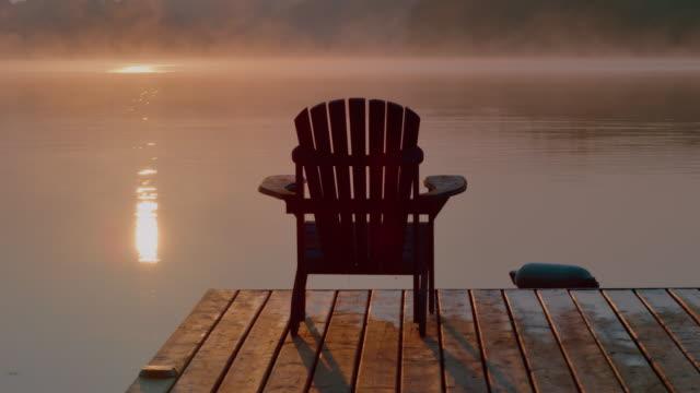 muskoka stuhl auf einem hölzernen dock an einem see bei sonnenaufgang oder sonnenuntergang. - landhaus stock-videos und b-roll-filmmaterial