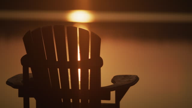 Video Muskoka chair on lake at sunrise or sunset. Starts still then has movement.