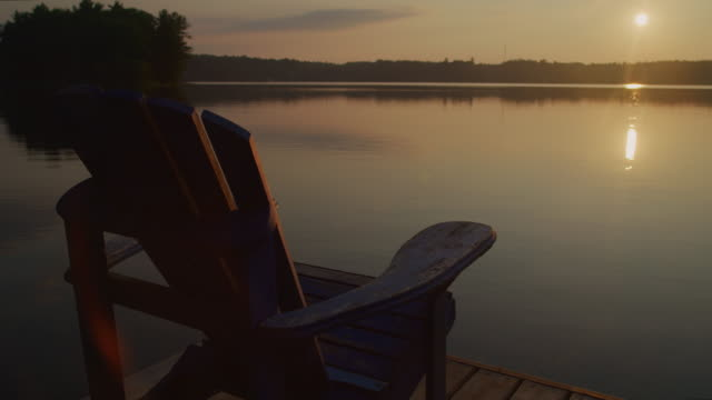 muskoka chair sits on a dock by a lake looking out toward the sunrise or sunset. - molo video stock e b–roll