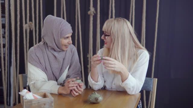 muslimska och kaukasiska kvinnor sitter i ett kafé. - anständig klädsel bildbanksvideor och videomaterial från bakom kulisserna