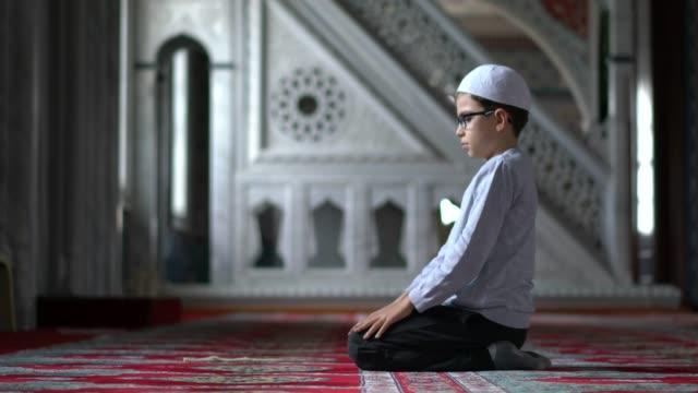 muslim boy praying in mosque - islam filmów i materiałów b-roll