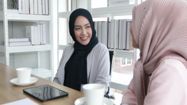 Muslim business woman in traditional clothing working and discussing at meeting and drinking coffee in office video