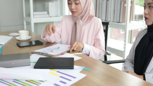 Muslim business woman in traditional clothing working and discussing  serious at meeting