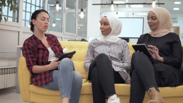 Muslim explain business stuff sitting on sofa in startup coworking office