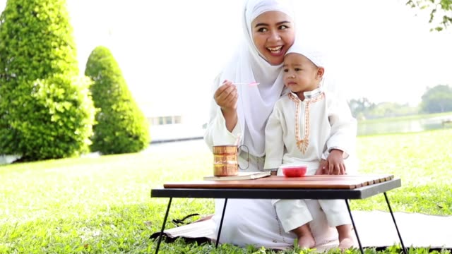 muslim family kids and mother relaxing and picnic at park. - abbigliamento modesto video stock e b–roll