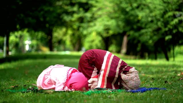 stockvideo's en b-roll-footage met moslim familie gebed voor god. moslim moeder en kind op hun knieën bidden god - koran