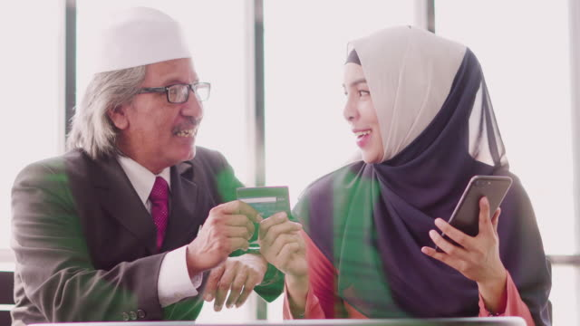 muslim father and daughter shopping online with credit card and smartphone. - holiday and invoice family video stock e b–roll