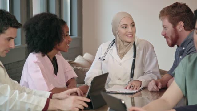 muslimsk kvinna läkare leder multietniskt medicinska team mcu - hijab bildbanksvideor och videomaterial från bakom kulisserna