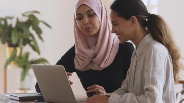muslimska kvinnliga mentor hjälpa kaukasiska praktikant förklarar datorarbete - hijab bildbanksvideor och videomaterial från bakom kulisserna