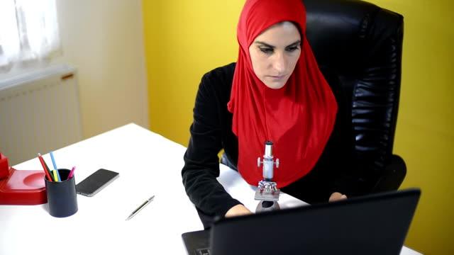Muslim female science working. video