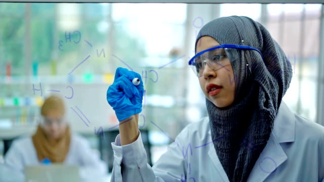 Muslim Female Scientist Drawing Formula Chemical On Transparent Board And Looking To The Camera