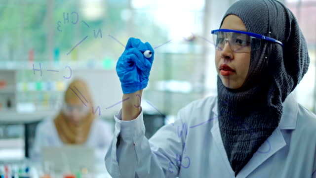 4K Muslim Female Scientist Drawing Formula Chemical On Transparent Board In Laboratory