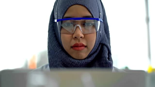 4k muslim kvinnlig vetenskapsman med hjälp av en bärbar dator arbetar forskning i laboratorium - hijab bildbanksvideor och videomaterial från bakom kulisserna