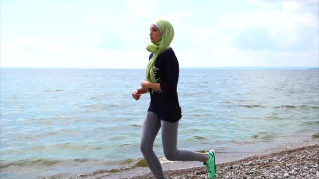 Muslim girl having jog training on pebble beach video