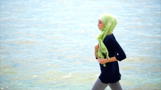 Muslim girl having jog training on pebble beach video