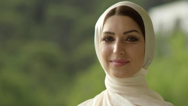 muslim girl in hijab is looking at camera - arab стоковые видео и кадры b-roll