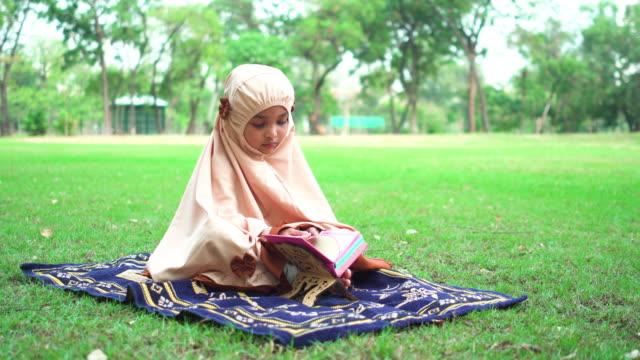 stockvideo's en b-roll-footage met moslim meisjeszitting om koran bij openbaar park in weekend te lezen - heilig geschrift