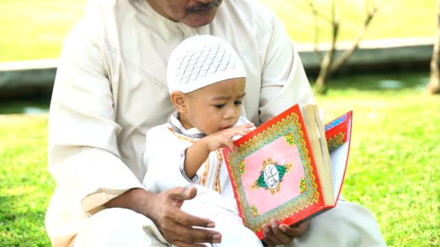 stockvideo's en b-roll-footage met moslim grootvader onderwijs zoon lezen van quran openbaar park in ochtend in zonlicht - koran