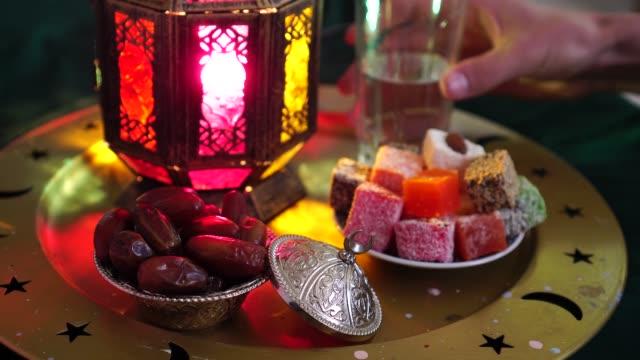 en muslim är dricks vatten för att bryta snabbt. fastan månaden ramadan. iftar-tabellen. glas vatten, dadlar, torkade frukter, sötsaker - ramadan lykta bildbanksvideor och videomaterial från bakom kulisserna