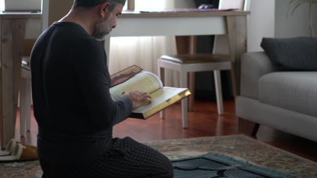 stockvideo's en b-roll-footage met moslim man leest de koran thuis - koran