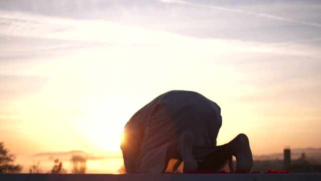 hd: muslim człowiek prostrating na wschód słońca - islam filmów i materiałów b-roll