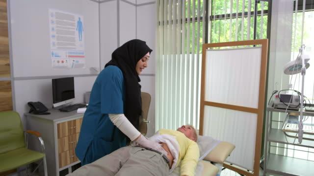 muslim medical worker doing abdomen palpation - abbigliamento religioso video stock e b–roll