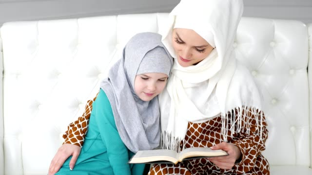 muslim mom in hijab is reading her little daughter a book sitting on the sofa. - fiaba video stock e b–roll