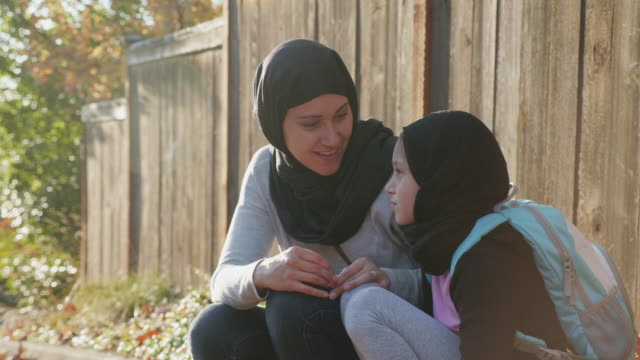 muslim mother and daughter sitting on a curb - hijab video stock e b–roll