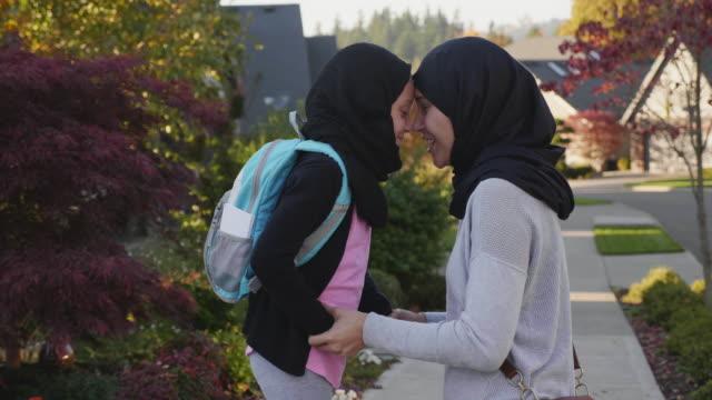 vídeos y material grabado en eventos de stock de madre musulmana de rodillas junto a su hija - islam