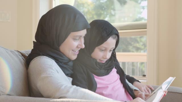 vídeos y material grabado en eventos de stock de 4k uhd: lectura musulmana madre a su hija - islam