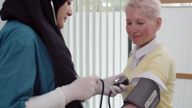 muslim nurse measuring pressure using tonometer - abbigliamento religioso video stock e b–roll