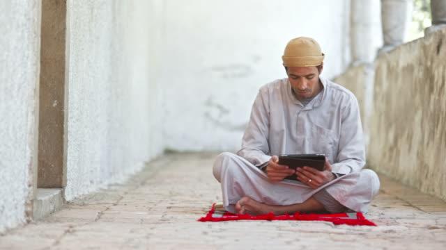 stockvideo's en b-roll-footage met hd dolly: muslim pilgrim using digital tablet - koran